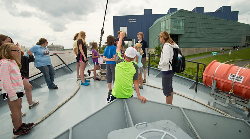 Figure 10. What better place to learn about lakes than aboard a big boat? Here, a party hears about some of the Blue Heron's scientific adventures while the boat is tied up in Duluth harbor at a Science on Deck event.
