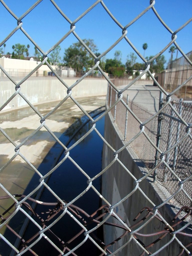The Forsaken River. The river appears behind a chain link fence.