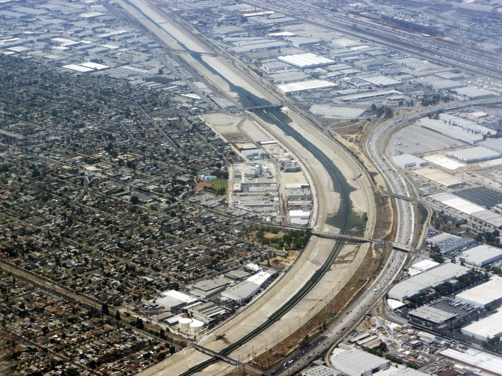 Aerial view of the Los Angeles River adjacent to a meandering highway.