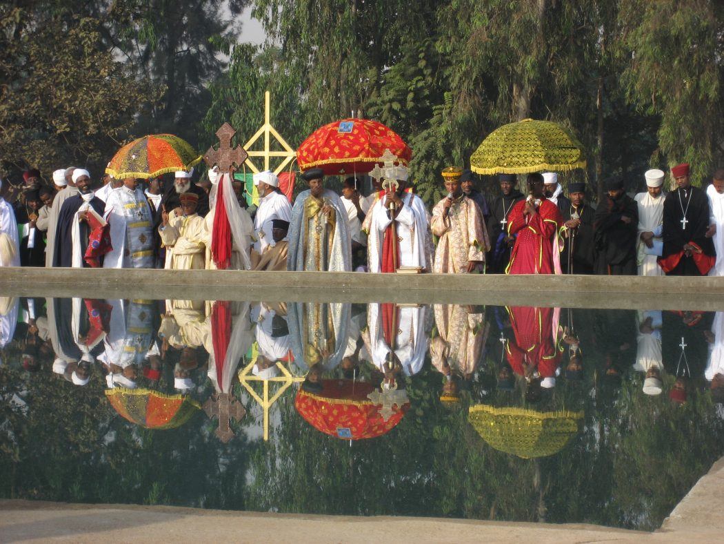 People gather for a religious ceremony near the water.