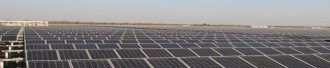 A large expanse of solar panels are being baked by the sun.