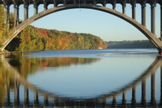 The fall colors along the Mississippi River are framed nicely by the Ford bridge. This photograph was taken looking upstream of Lock and Dam 1 in Minneapolis, Minnesota. USACE photograph by Sam Mathiowetz.