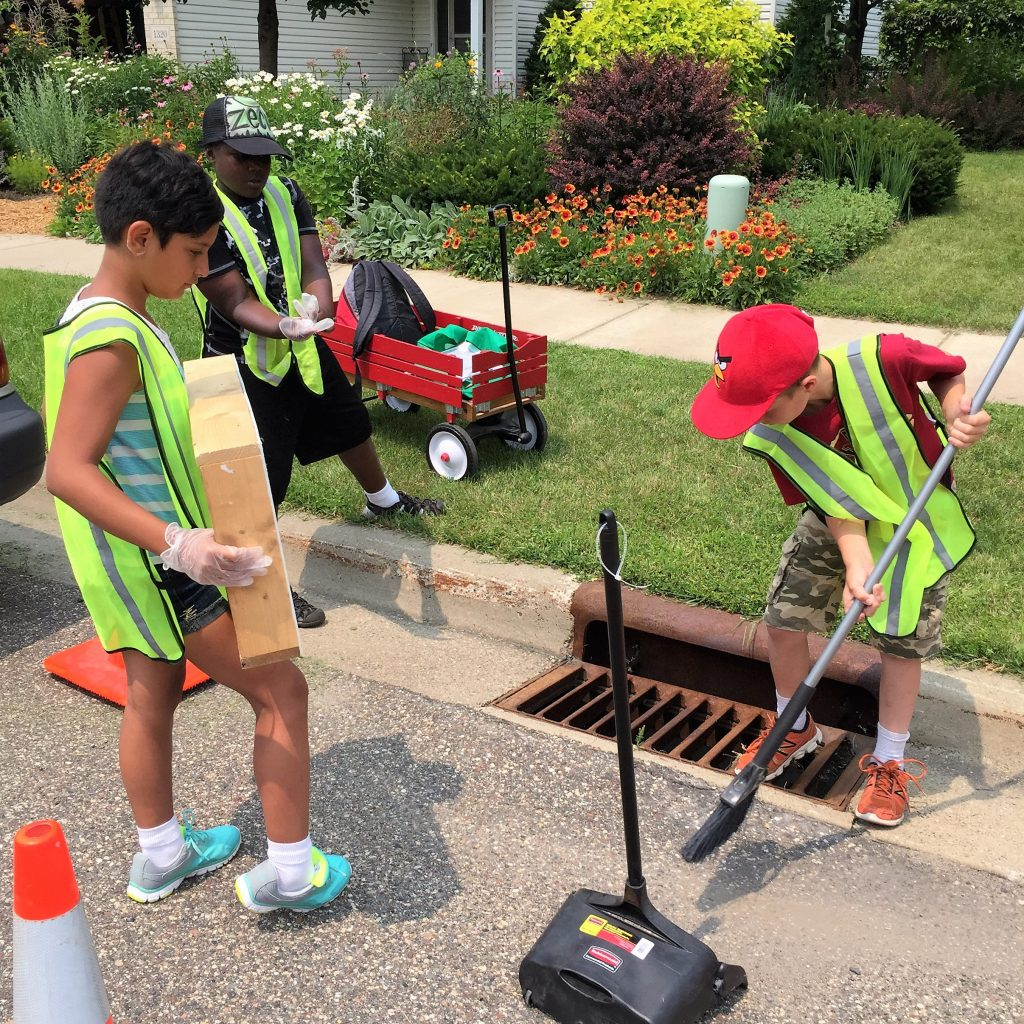 Northfield youth sweep clear then stencil stormdrains that empty into the Cannon River. Image courtesy of CRWP.
