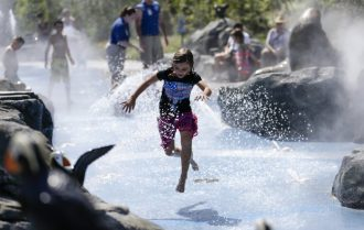 A youngster cools off at the Alaskan Adventure splash pad at the Henry Doorly Zoo in Omaha, Neb., Thursday, July 21, 2016, as high temperatures and humidity affect much of the central U.S., making it feel as hot as 115 degrees Fahrenheit in some places and leading some cities to open cooling stations and take other precautions.