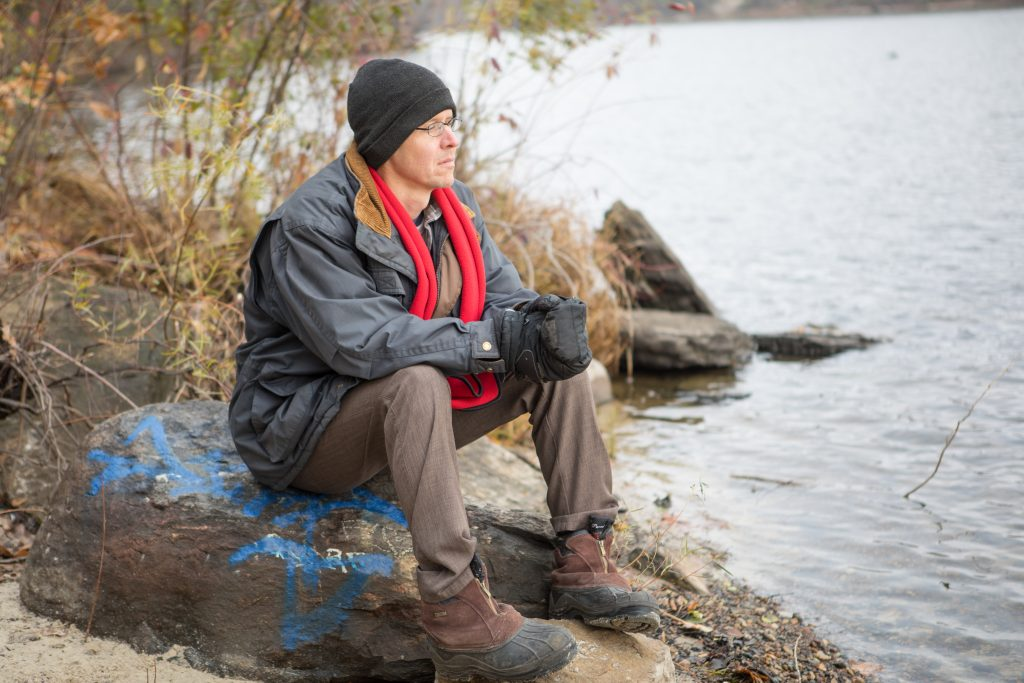 Michael Bischoff reflects near the river's edge.
