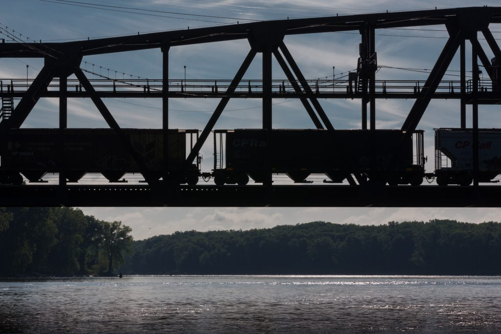WTTR summer 2017 submission 'Lonesome whistle' over the Mississippi River at Hastings, MN, near several FMR habitat restoration and Vermillion Stewards volunteer sites. The silhouettes of three train cars appear on a bridge crossing the river.