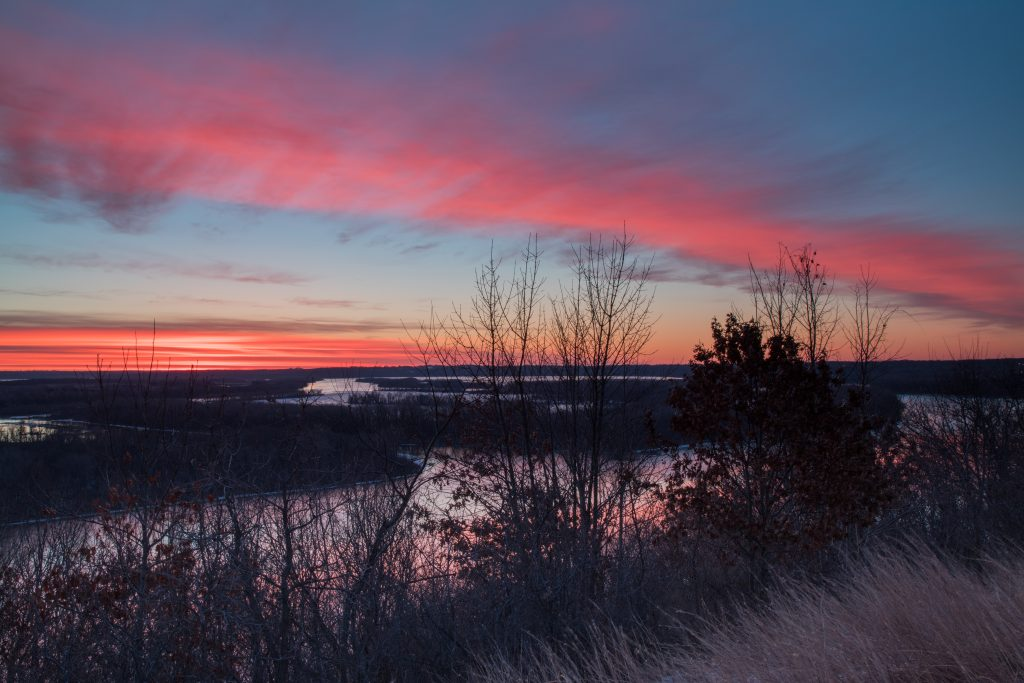 'Morning Color' at Pine Bend Bluffs SNA in Inver Grove Heights, MN one of FMR's most popular protection and restoration sites. The sun rises over the river, causing the sky to be painted with a variety of oranges and pinks.