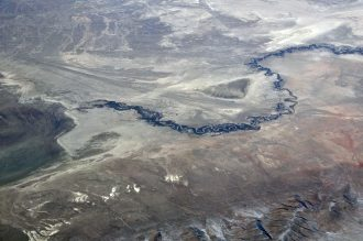 Aerial shot of a river flowing through an extremely dry environment.
