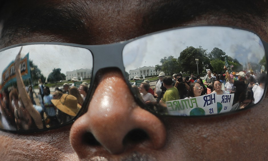 A group of environmental protesters are reflected in someone's sunglasses.
