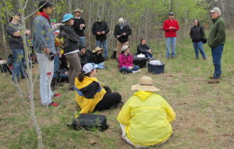 Figure 3. Archaeologist Doug Birk speaking to St. Cloud State University anthropology students enrolled in the author's 2014 archaeological field school at the Little Elk River Mission site. Image courtesy of the author.