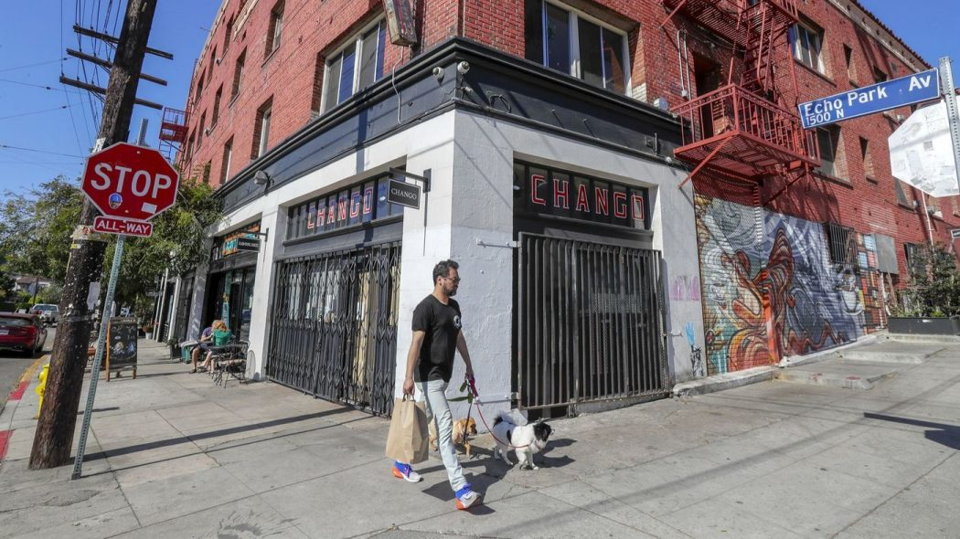A man walks his dog in front of an abandoned storefront.