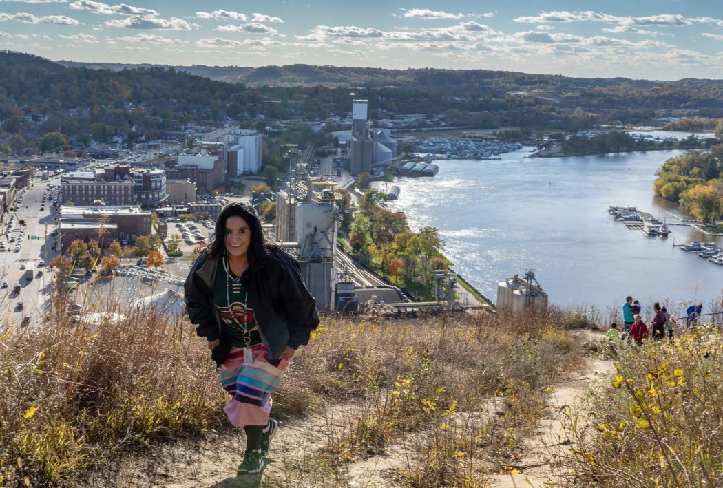 Someone wearing a Minnesota Wild jersey climbs to the top of a hill looking over Red Wing, MN.