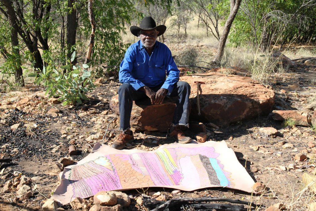 Ngarralja Tommy May with his art work Untitled, synthetic polymer and paint pen on sheep hide, 2018. Courtesy Mangkaja Arts Resource Agency.