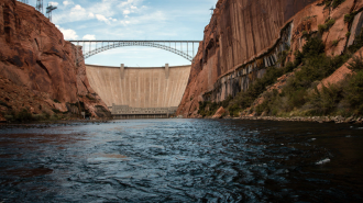 A shot of a large dam with a bridge passing above it.