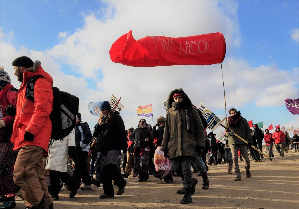 Marches north on Highway 1806 to the Backwater Bridge militarized barricade and back through camp were part of actions to hold prayerful space and bring attention to the threat of the Dakota Access Pipeline. November 1, 2016. Image courtesy of the author.