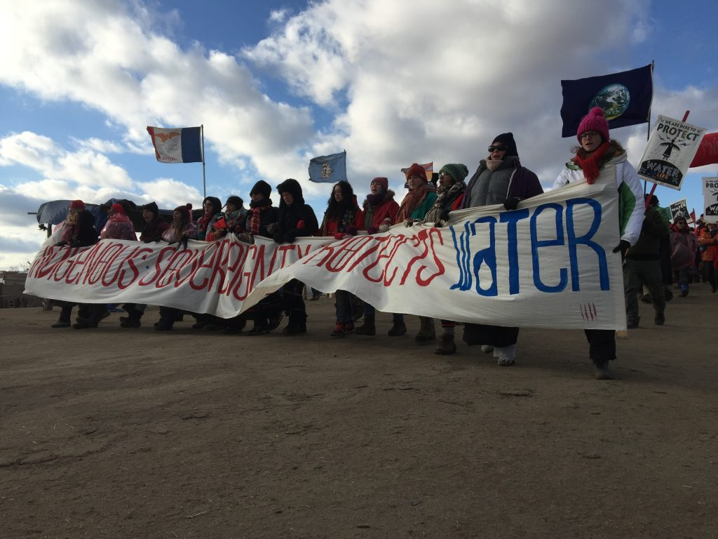 Groups of Water Protectors march through camp with banners that read 'Mni Wiconi' and 'Indigenous Sovereignty Protects Water.' Image courtesy of the author.