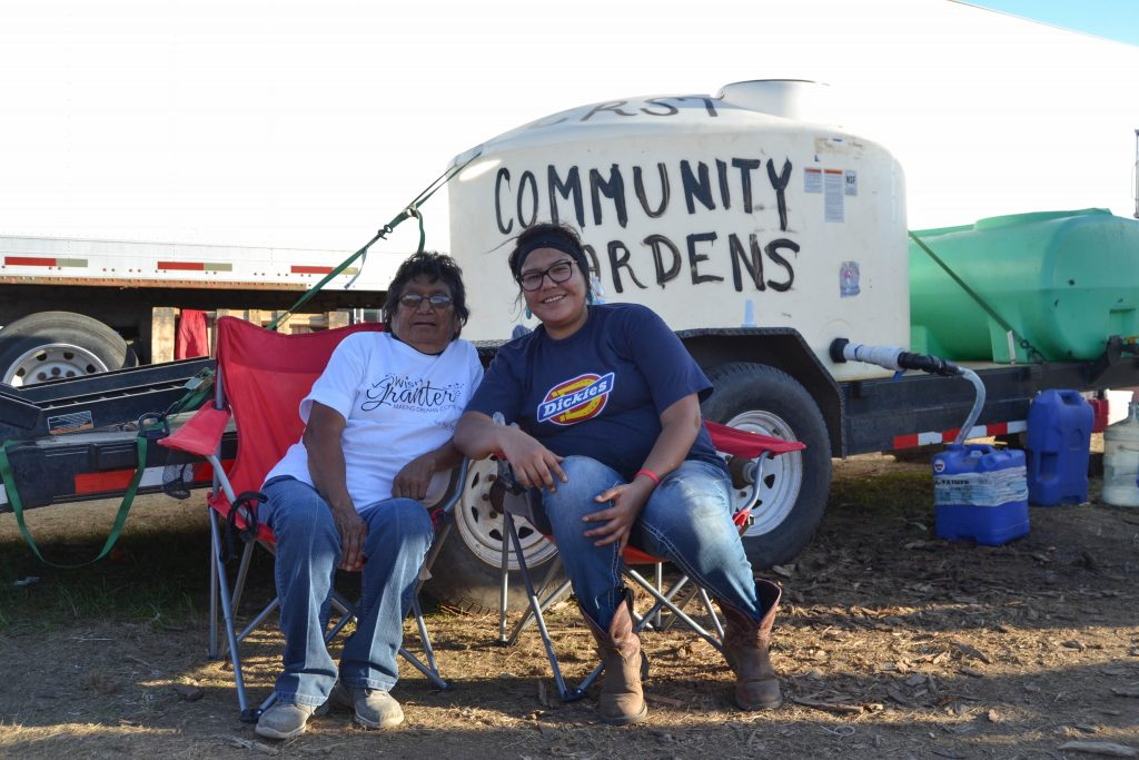 Two womxn rest next to Community Gardens water tank at camp. Image courtesy of Kyra Antone.
