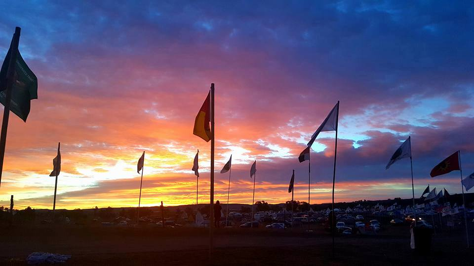 Tribal treaty flags standing against the evening sky. Standing Rock is noted as a time when Indigenous nations from across the country and world came together in an unprecedented united front.