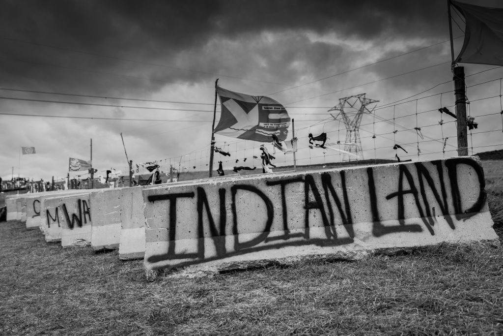 Reminiscent of graffiti on Alcatraz Island, Indian Land is written across a concrete divider. Dividers were used as barricades to stop water protectors nearing construction of the DAPL pipeline. Image courtesy of Alex Flett.