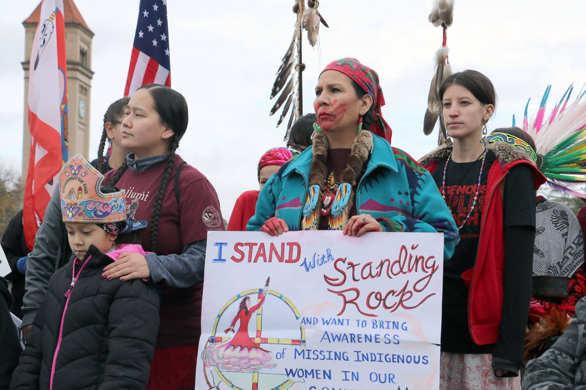 Highlighting the link between the Water Protector movement and the MMIW movement, Ann Ford (Coeur d'Alene) at the Indigenous Peoples March in Spokane, WA 2019, holds a march poster that reads, 'I stand with Standing Rock and Want to Bring Awareness of Missing Indigenous Women in our Country.'