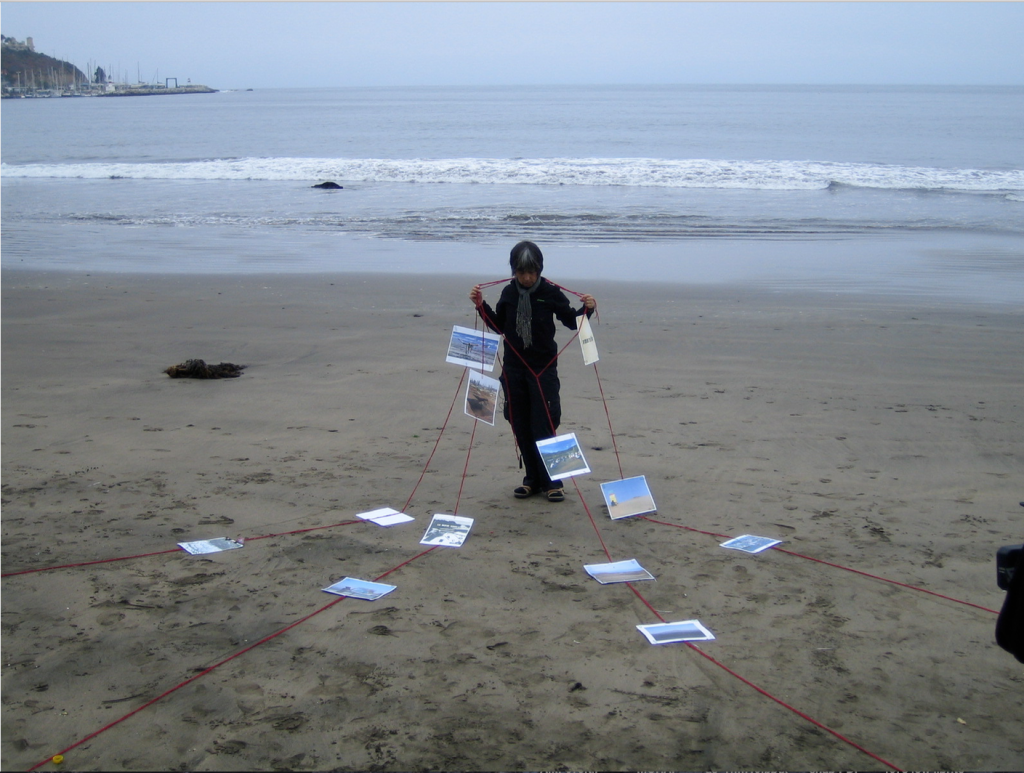 Images on lines, screenshot from 'Kon Kón.' A person standing on a beach is loosely wrapped in red string, and photos are attached to the strings.