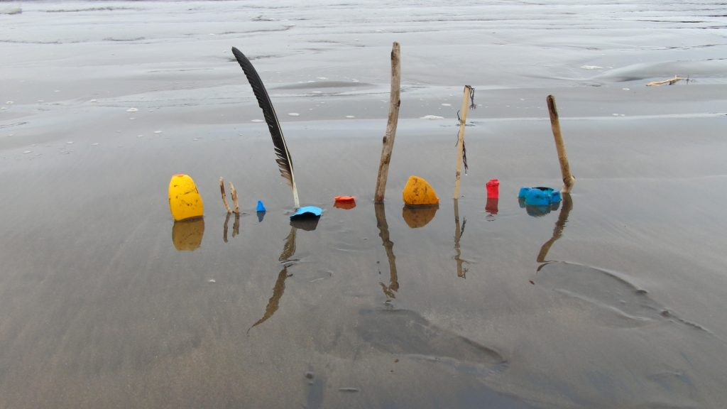Kon Kón' found object sculptural edge, photograph by James O'Hern. Twigs, pieces of trash, and feathers are stuck into the ground and standing upright at the water's edge.