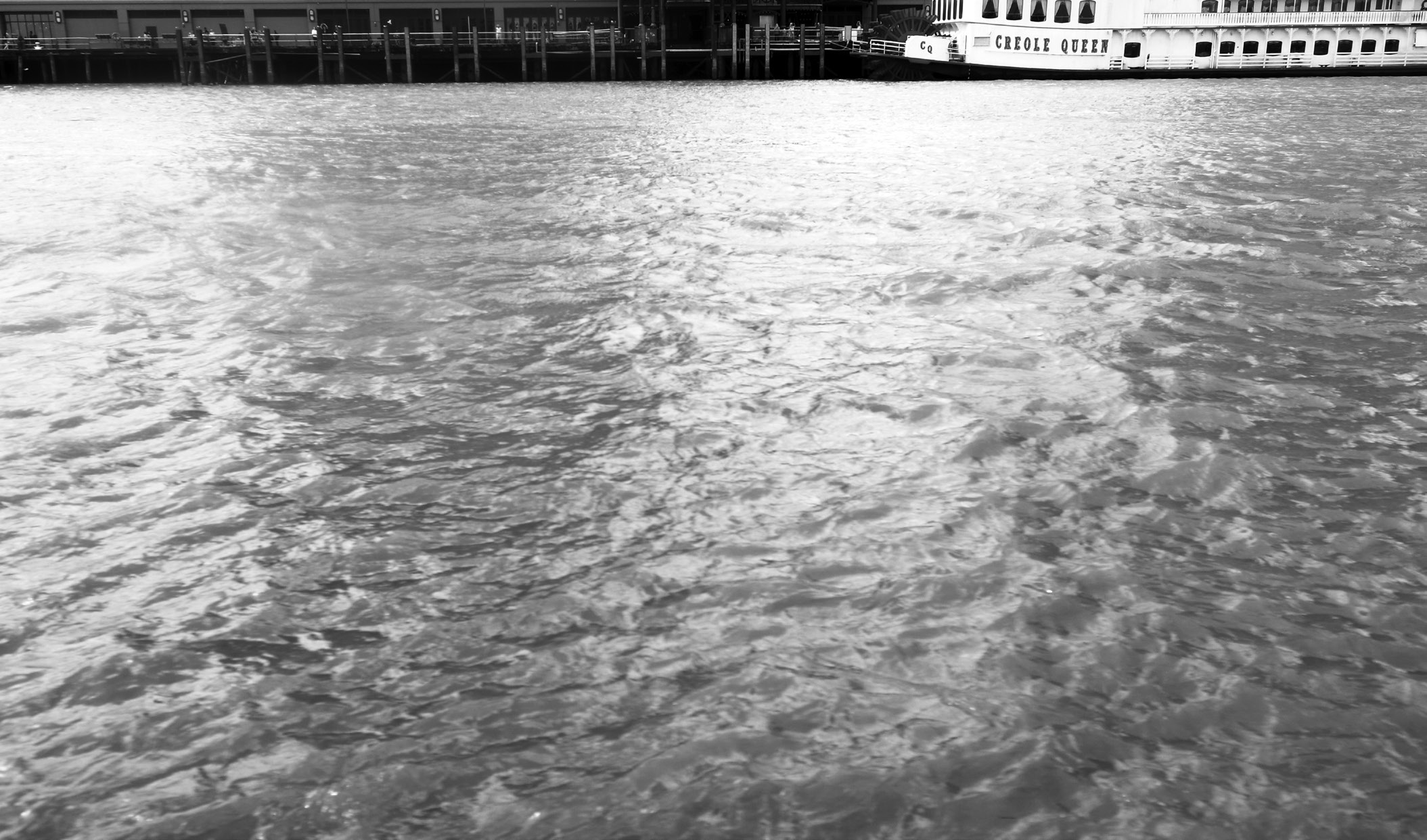 Black and white shot of a river. A large passenger boat named 'CREOLE QUEEN' appears in the distance.
