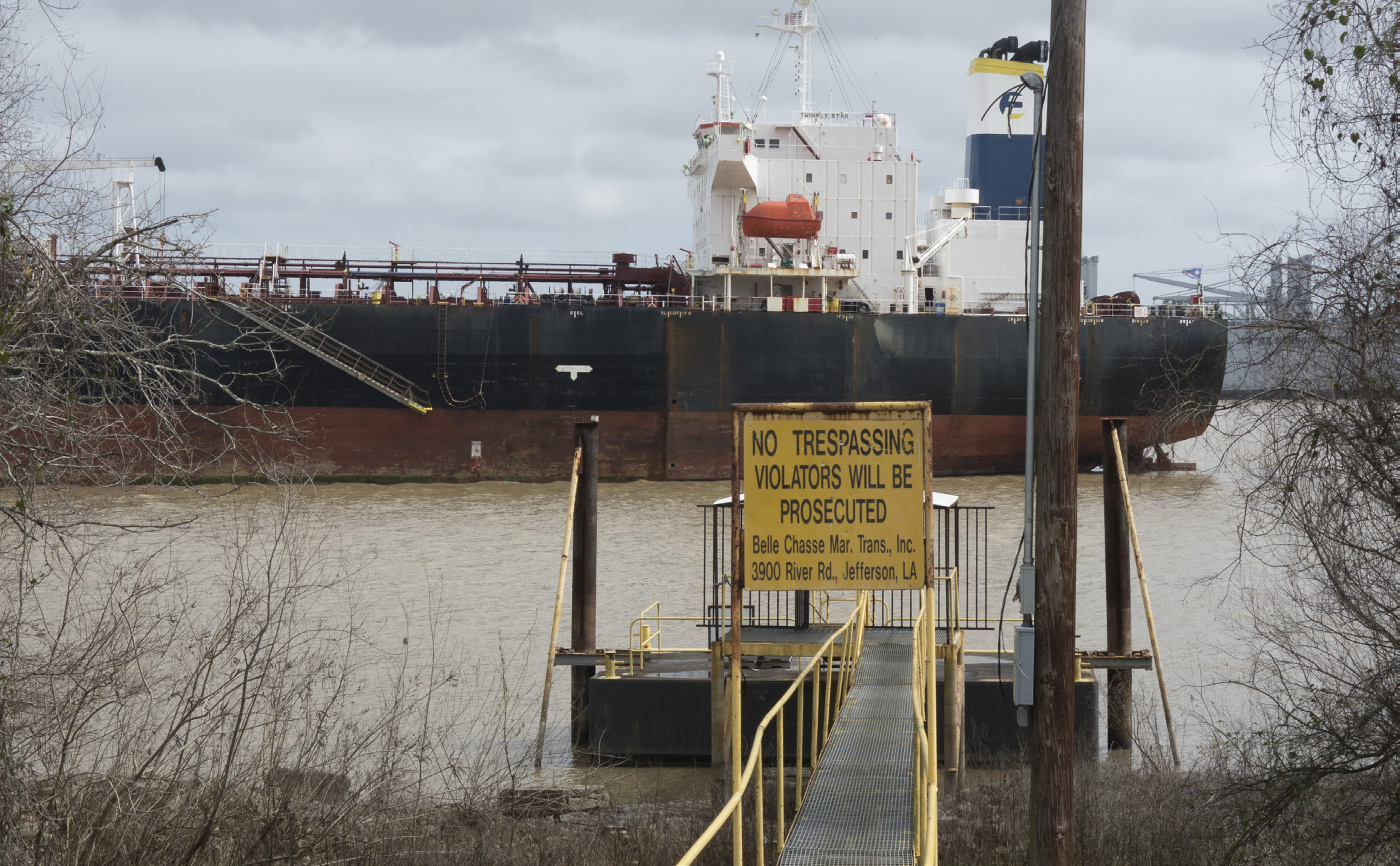 A sign reads 'NO TRESPASSING, VIOLATORS WILL BE PROSECUTED. Belle Chasse Mar. Trans., Inc. 3900 River Rd., Jefferson, LA.' that leads to a dock. A large barge is also in the photo, in the distance.