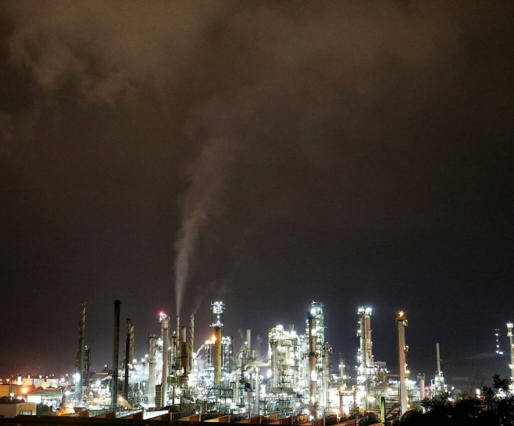 Aconcagua Refinery. Smoke rises towards the sky in a brightly lit industrial area at night.