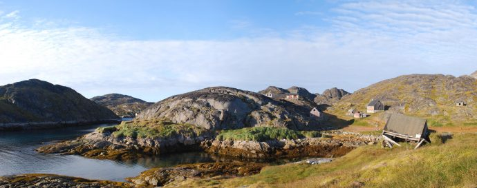 A few old houses sit on a rocky shore. The settlement of Kangeq in Southwest Greenland was abandoned in the 1970s. The site has been occupied for thousands of years.