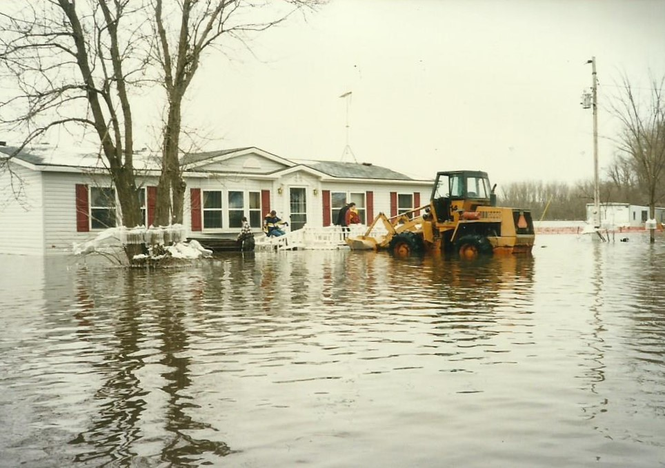 Sara Blue's house during the flood of 1997. A large bulldozer-like vehicle faces the house, and the water level seems to be at the same level as the very bottom of the front door. Image courtesy of Alex Blue.