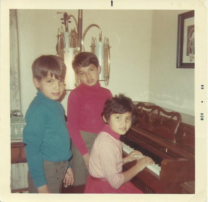 The Blue siblings James Blue (left), Alex Blue (center), and Laurie Blue (right, playing the piano). The piano in question was one of many sentimental items lost in the flood as described in Laurie's interview. Image courtesy of Alex Blue.