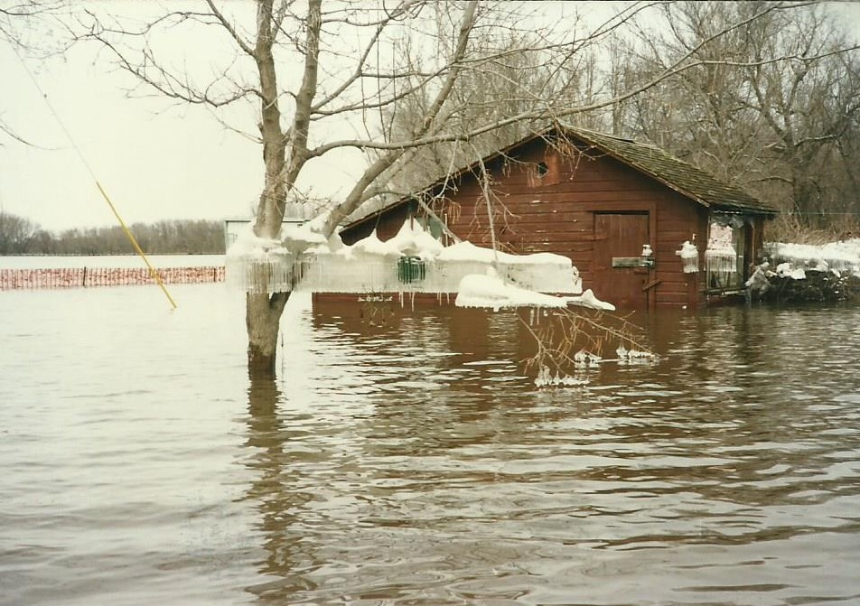 Chicken coop in floodwaters. The chicken coop was torn down a few years after this. The ice on the trees indicates where the floodwaters were just a day before. The water seems to have decreased around 4 feet in one day. Image courtesy of Alex Blue.