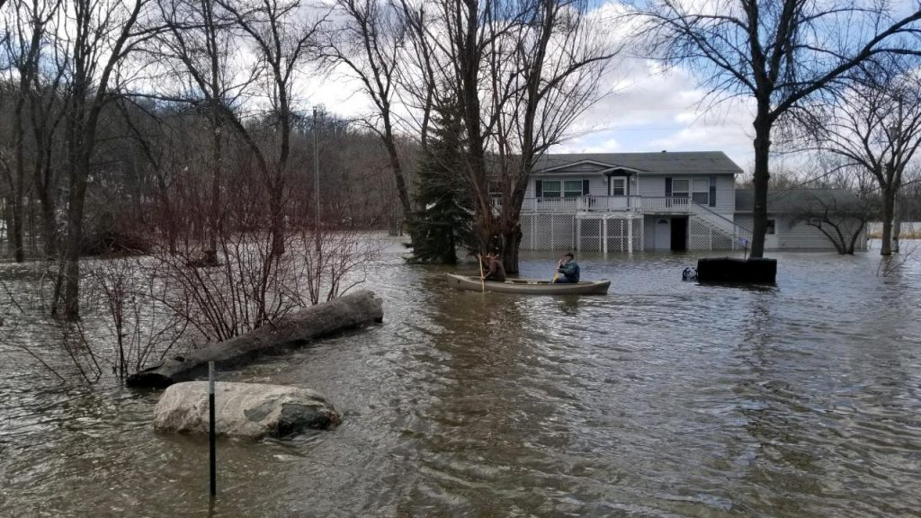 A house looks to be submerged under a few feet of flood water from the outside. Someone is able to use a canoe to navigate around right in front of the house.