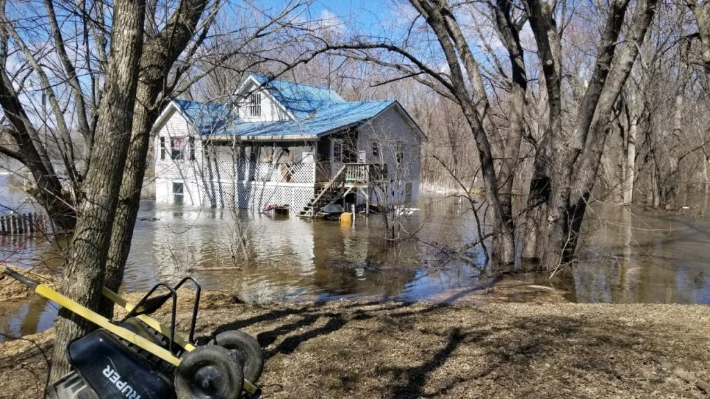 A house looks to be submerged under a few feet of flood water from the outside.