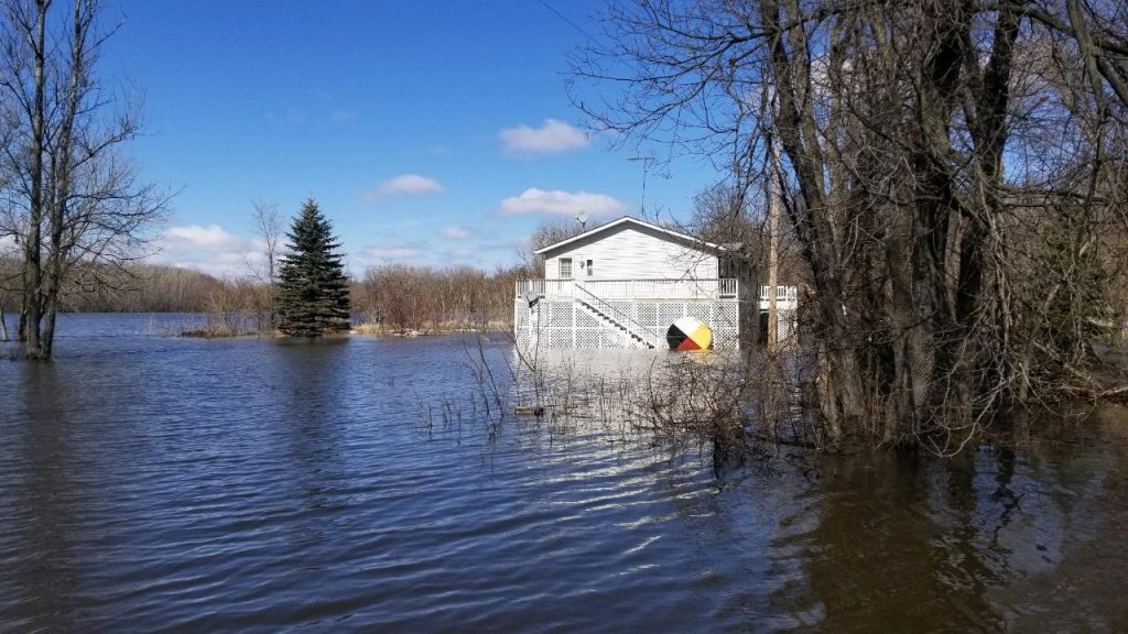 A house looks to be submerged under a few feet of flood water from the outside