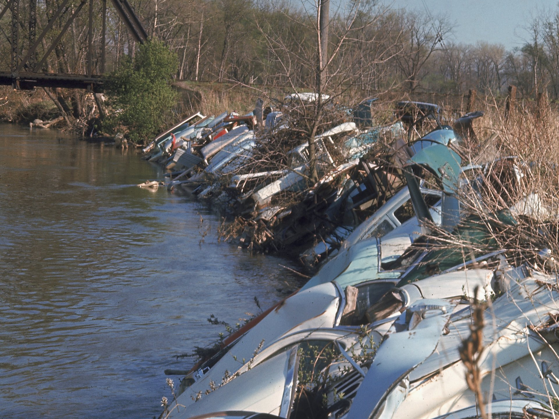 Vintage EPA photos reveal what US waterways looked like before pollution was regulated. The bank of a river is littered with old broken cars.