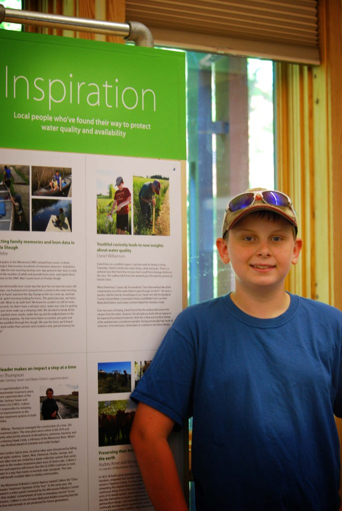 Daniel Williamson stands next to his featured story. Daniel was one of six people featured in the Prairie Woods Environmental Learning Center/Spicer exhibit.