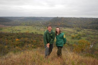 Whitewater State Park naturalists Jeremy Darst and Sara Holger pose on Seibenaler Ridge overlooking the Whitewater River in the Whitewater Wildlife Management Area. The naturalists are the story keepers for the Whitewater valley. They share the valley history so that others might learn from the past and make better choices for the future.