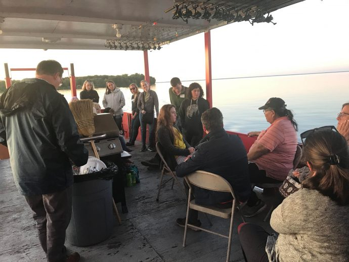 A group of people are on a large boat with a flat gathering area. They are all listening to an instructor.
