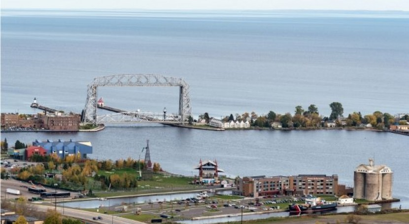 A lift bridge in Duluth is shown from a low angle aerial, showing the lake in the distance and the city on the near shore.
