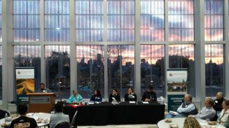 A group of speakers sit at a long table, surrounded by attendees around round tables. Background is tall windows showing a skyline and colorful sunset.