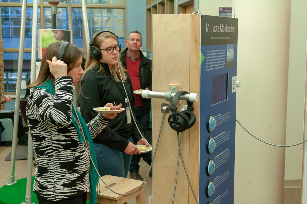 Visitors to the exhibit at the IonE listen to narratives.