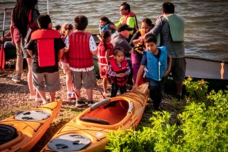 Children and adults get ready to launch canoes and kayaks June 12, 2019, on the Cedar River State Water Trail at Austin Mill Pond as part of Austin's second annual 4th Ave Fest. Cedar River Watershed District and the Jay C. Hormel Nature Center served about 120 individuals with free canoe and kayak rentals as part of the event and their We Are Water MN programming. Image courtesy of T. C. Rietz.
