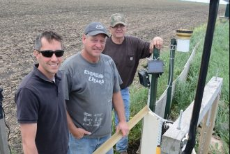 "Kevin Kuehner, MDA hydrologist and researcher (left), Wayne DeWall, participating farmer (center), and RRFSP walkover technician Ron Meiners (right) pause at the edge-of-field monitoring station in DeWall's field. Data collected at this station over many years is now informing on-farm management decisions throughout the region. Image courtesy of Paula Mohr, ""The Farmer"" magazine."