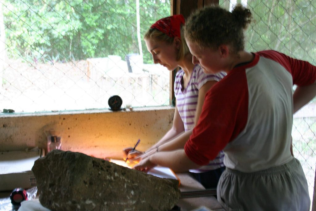 From left, Sarah Van Oss (College of Wooster Class of 2016) and Haley Austin (College of Wooster Class of 2016) seen documenting a stela fragment at the site of El Perú-Waka' in 2015. Image courtesy of Keith Eppich.