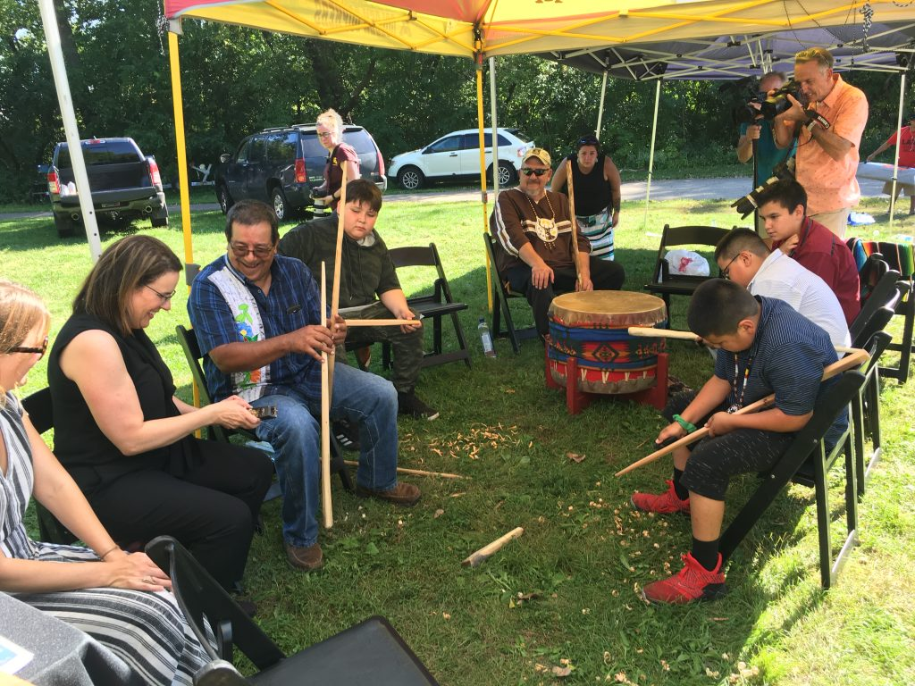 Joe Graveen shows President Gabel how to carve manoomin ricing sticks near the Wigwam Jrs. drummers. Clockwise, from left: Bree Duever, Manoomin Project coordinator; President Gabel; Graveen; Tristan Mustache, drummer; John Johnson, Sr., Lac du Flambeau project partner; Edward Poupart, Lac du Flambeau, Wigwam Jrs. drummer; Elliot Johnson, drummer, and Ganebik Johnson, drummer. Image courtesy of Laura Matson.