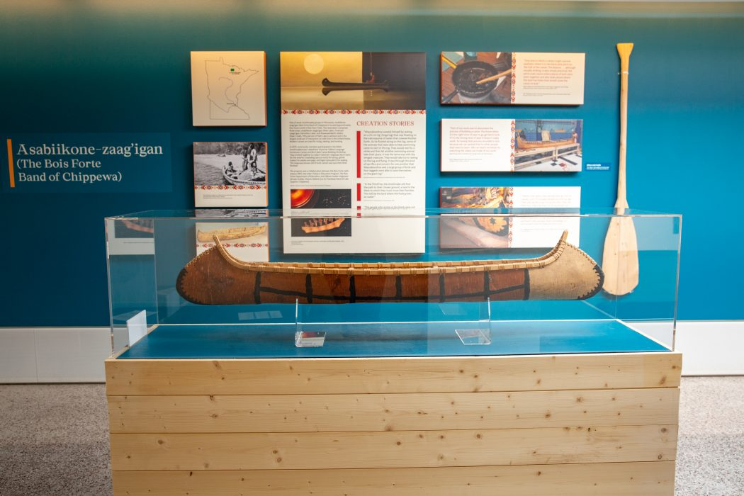 From the exhibit, a canoe, paddle, and creation stories from the Asabiikone-zaa'igan (The Bois Forte Band of Chippewa). Image by Laura Mazuch, UMN Printing Services.