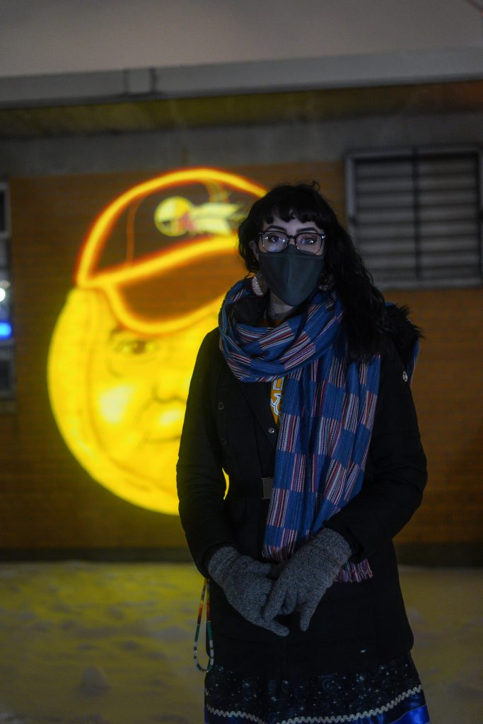Artist Moira Villiard stands in front of the mini projections. Image courtesy of Nedahness Greene.