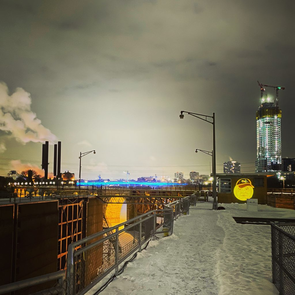 A photo taken on the night of testing the projectors, Minneapolis glows in the distance as the Mishomis (Grandfather) animation appears on one of the lock site's smaller walls. Image courtesy of Moira Villiard.